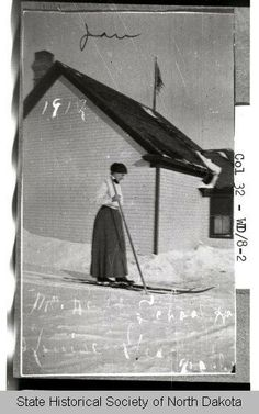 January 1912: Teacher on skis, Ward County, N.D. A teacher on skis outside a small rural schoolhouse. The flagpole and flag can be seen at upper center. The ground is completely snow covered.