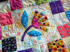 Quilt Art | Detail of hand quilting around flowers.