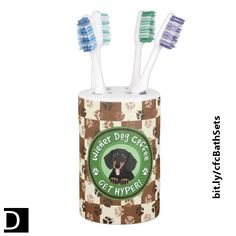 """This cute toothbrush holder comes with a matching soap dispenser and features an adorable brown and black dachshund peeking out of the center of a green circle around which are the words """"Wiener Dog Coffee"""" and """"Get Hyper!"""" separated by paw prints. The background is littered with paw prints in various shades of brown above a checkerboard of coffee and cream colored blocks. #StudioDalio #bathaccessories #bathroomdecor #doglovers #pawprints #coffeehumor #toothbrushholders"""