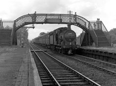 The engine of a train bound for Yarmouth comes under the footbridge at Whitlingham Junction and approaches the derelict station platforms. The station had been closed in 1954, but the footbridge, built in 1886 remains to this day, providing access to the marshes. It is around 1960, and the train is one of the many which ran on Saturdays in the Summer, bringing holidaymakers to Yarmouth from far and wide, from the north, the Midlands and London. Engines of this type were normally be used on…
