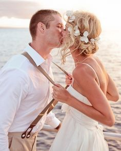 a groom with suspenders & the bride with flowers in her hair...