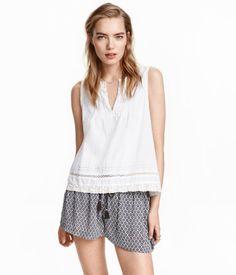 Kurze Shorts aus weichem Webstoff. Die Shorts hat einen elastischen Bund, einen Kordelzug mit Quasten und Seitentaschen.