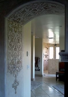 FORMAL TO KITCHEN & MASTER  A Modello® stencil in an arch (EasPan105). Project by Tamra Cook. Panel over metallic plaster designed to look and feel like aged worn silk