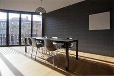 De warme bamboevloer en ruwe betonmuren in de eetkameren contrasteren met de strakke benedenverdieping.