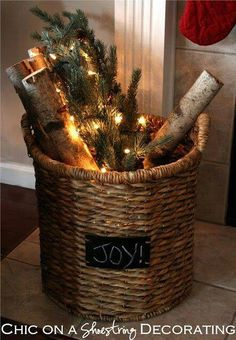 logs, evergreen branches and lights in a basket by the fireplace
