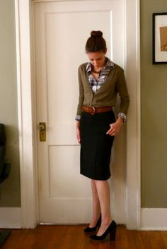 black pencil skirt with a plaid blouse, olive cardigan, and wide brown belt.