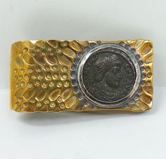 This is a handsome gentleman's money clip from the American studio jeweler William Tripp. The clip is superbly crafted in hand hammered brass with sterling silver accents. The clip features an ancient Roman coin depicting Emperor Valens (328-378), which is surrounded by a richly textured surface.
