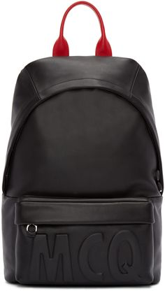Structured buffed leather backpack in black. Carry handle in red at top. Adjustable grosgrain shoulder straps. Zippered compartment at face featuring tonal raised logo. Two-way zip closure at main compartment. Zippered pocket at interior. Tonal textile lining. Silver-tone hardware. Tonal stitching. Approx. 11.5