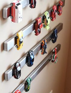 What a fun storage solution for a child's toy car collection! Just mount magnetic knife strips to the wall! Easy organization and a cute display!
