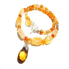 A faceted pear-shaped cognac citrine pendants gives this stunning toggle necklace a warm tone that is sure to catch the eye of everyone in the room. Accented by smaller beads and rough-cut citrine and agate, this necklace is ideal for any formal event.