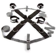 """Croce e manette da letto """" 50 sfumature di grigio"""".Questa croce è adattabile a tutte le dimensioni dei letti. Basta far passare sotto il materasso le fasce di tenuta. Attraverso anelli e moschettoni si possono fare varie forme di bondage"""