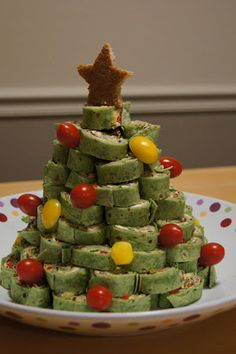 I used this Christmas tree design because I brought them to a holiday party!  INGREDIENTS: 8 oz. cream cheese, softened 2 cups shredded mild cheddar cheese 1 cup (8 oz.) diced green chiles 1 cup (about 6) sliced green onions 1/2 cup chopped black olives 1 cup diced red bell pepper 1 1/2 tsp. Southwestern seasoning (optional. I used Pampered Chef brand.) Deli sliced turkey 8 12-inch spinach tortillas Salsa (for dipping) One slice of toasted bread Cherry tomatoes Yellow bell pepper