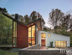 Architect Robert M. Gurney designed this house with a dramatic wall of polished concrete blocks at the entrance. The butterfly roof volume features exterior grade mahogany, while the lower area is sheathed in Galvalume zinc-coated steel sheets.