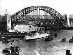 Sydney Harbour Bridge nears completion as ferries and boats pass. 🌹