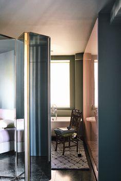 Côté salle de bains, une petite chaise dans le goût chinois de 1900 et une lampe d'Oscar Torlasco (Galerie Artefact Design) sont posées sur un tapis en laine (Codimat). Au second plan, la fenêtre d'albâtre qui apporte de la lumière naturelle venue du salon.
