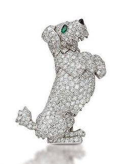 """AN UNUSUAL DIAMOND DOG BROOCH, BY CARTIER . They describe the pin: """"Designed as an articulated begging terrier with emerald eyes and onyx nose, a mechanism on the reverse allows the paw and tail to move, 4.2 cm, with French assay mark for platinum and gold, in red leather Cartier case."""" Price realized at auction was $62,937."""