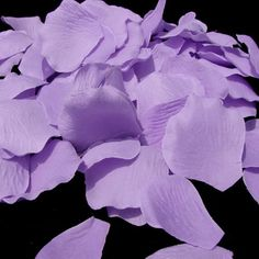 Lavender rose petals scattered under center pieces that match color of the cake.