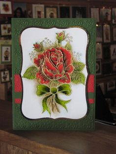 handmade card ... gorgeous rose embossed in gold ... beautiful coloring ... nice shadowing around the image ... embossing folder texture over background including two bands of red paper ...  luv it!