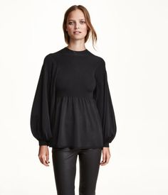 Soft, fine-knit sweater with long balloon sleeves, seam at waist, and gentle flare to hem.
