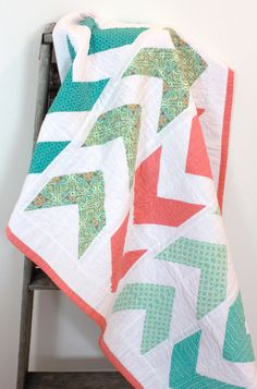 Baby girl crib quilt, arrow design. Quilt made using entirely 100% cotton fabrics, as well as 100% cotton quilt batting. Main colors in the