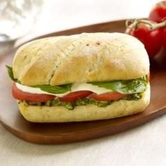 Mini baguettes spread with pesto are filled with tomato and mozzarella slices, then heated until warm and cheese is melted.