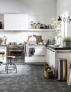 vtwonen keuken; wit, betonnen aanrechtblad, tegels in de keuken, lange grepen geschikt voor het ophangen van theedoeken, open planken, spider kruk