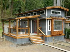 Great looking little cottage with deck. Love the high roof and windows.
