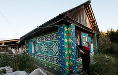"""in the remote village of Kamarchaga, located in the Siberian Taiga, Russian pensioner Olga Kostina has decorated her wooden home with colorful patterns and images made from over 30,000 plastic bottle caps"""