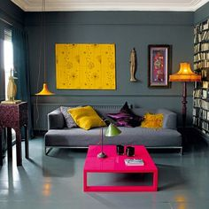 Grey living room with yellow and pink accents and a fake book wall