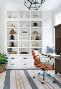 White drawers accented with oil rubbed bronze pulls are fixed beneath built-in styled white shelves in a home office illuminated by a glass and brass pendant hung over an orange and gray striped rug   Bria Hammel Interiors