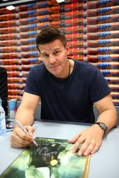 Bones star David Boreanaz signs posters for fans at Comic-Con 2012.