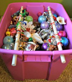 To make this smart storage, just drill holes into the sides of a plastic bin and fit a wooden rod through the openings. Then loop hangers onto each rod so that next year when you're ready to decorate the tree you'll know each ornament is ready to go.