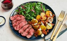 Spanish Steak & Patatas Bravas drizzled in a herb aioli with a baby arugula salad,