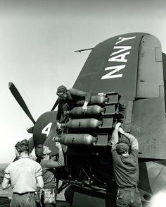 Ordnancemen place arming wires on 100-pound bombs mounted onto the wing of an F4U-4 Corsair on board the aircraft carrier USS Boxer (ca. 1950).