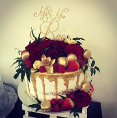 Gold and red how romantic. Semi naked sponge cake with gold drizzle gold macarons hand painted gold flowers and red roses. Perfect for a small interment wedding.