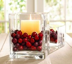 cranberries in a hurricane with a candle, beautiful. a bit of water helps keep the wax from locking the candle to the hurricane, too.