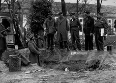 The alleged site of Adolf Hitler's grave behind the Chancellery in Berlin, with soldiers standing alongside the petrol cans thought to have been used to burn his body.