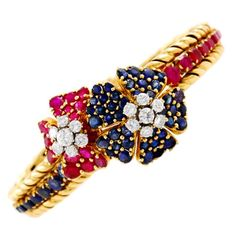 Beautiful 18kt yellow gold, rbuby, sapphire and diamond bracelet, with two flowers in the center, signed Mauboussin, 1950's.