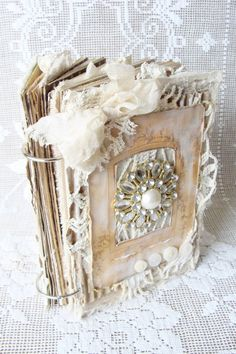Unique handmade book - Covers constructed from chipboard covered with remnants from a vintage doily, fabric, vintage album cover, corrugated cardboard, buttons and a large pearl and rhinestone cabochon. Contents Include over 40 (80) pages of alternating blank pages and cardstock from my tea dyed papers, pretty double sided papers, handmade envelopes, fabric pages and pockets, tags, journaling cards, ephemera, vintage and new laces, and much more. Lots of bits and pieces tucked in here and…