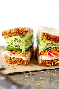 California Veggie Sandwich - There is nothing boring about this veggie sandwich! Work your way through layers and layers of bold flavors in this California veggie sandwich with pickled carrots, mashed avocado, lemony goat cheese spread, cucumbers, sprouts and baby spinach. Recipe, sandwich, snack, healthy, vegetables | pickledplum.com