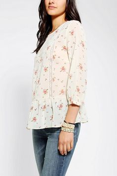 Freshly cut floral blouse from Pins and Needles with a ruffled hem and a button-down back.  Topped with a sheer mesh v-neck inset at the fro...