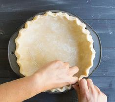 Hands fluting the edge of the Easy All Butter Pie Crust before baking from themerchantbaker.com