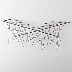 """A cross between abstract modern art and functional candle holder, this graphic steel wall decoration was inspired by a mountain landscape, with 16 flickering tealight or votive candles representing twinkling """"stars"""" above the horizon."""