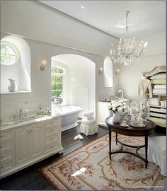Large, luxurious bathroom beautifully decorated with an area rug and an open French armoire for storage. #Frencharmoire
