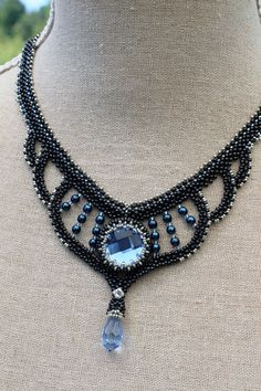 Beadwoven charcoal necklace with light blue chessboard cabochon and firepolished drop bead.