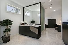 Sprawling marble floor bathroom features full separate vanity and makeup stations, all in dark stained wood cabinetry. Large mirror hangs on central marble shower enclosure with smoked glass doors.