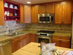 Full Height Back Splash using 4x4 Travertine and 1x1 bold glass accents. Really added some contrast and pizzazz to this kitchen. :)  Materials and Labor provided by Color Tile & Carpet of Salem, Oregon.