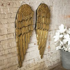 Dress up the wall with these charmingly rustic wings. Delicate feather patterns are layered in the wood, then painted bright, gleaming gold and uniquely distressed for a one-of-a-kind art piece.