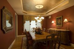 Glamorous Red And Brown Traditional Interior Decorating Idea For Dining Room With Red Wall, Brown Curtain, Floral Painting With Gold Frame, Brown Table With Flowers, Brown Chairs With Rd Seat Cushions, White Chandelier, Cream Red Rug, And Brown Wooden Floor Tile - Use J/K to navigate to previous and next images