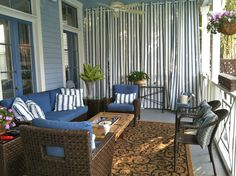Stylish Sunbrella curtain panels block UV light and blend with this charming porch decor.